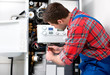 Technician servicing heating boiler - 62687938