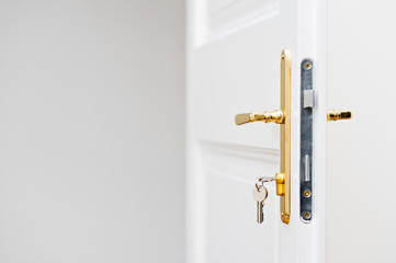 Keys in the keyhole with beautiful golden doorknob on white door