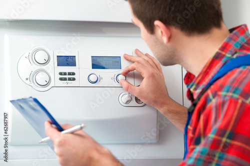 Technician servicing heating boiler - 62687917