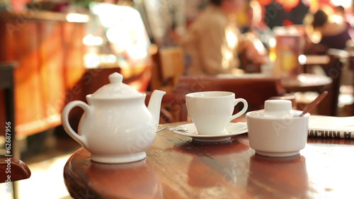 Teapot and sugar-bowl on the table in crowded cafe