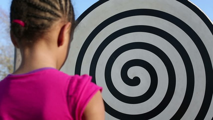 Young girl gazing at a hypnotic swirling design in a park