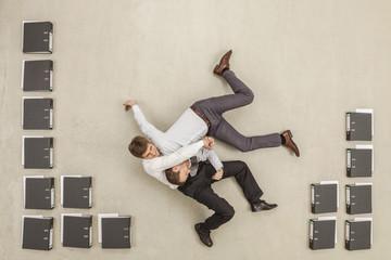 Geschäftsleute kämpfen im Büro zwischen Akten