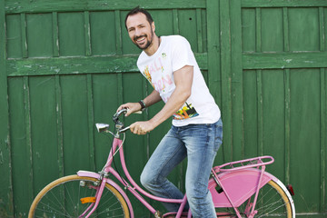 Deutschland, Bayern, Mann sitzt auf rosa Fahrrad