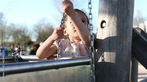 Young girl pulling a sand bucket in a playground
