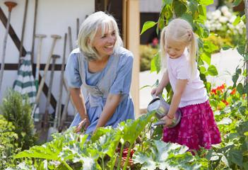 Deutschland, Bayern, Seniorin und Mädchen in der graden Pflege für Pflanzen