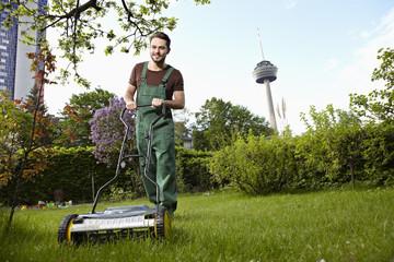 Deutschland, Köln, Junger Mann mäht Rasen mit Rasenmäher