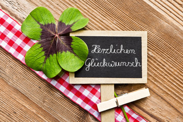 Holzhintergrund mit Tafel und Kleeblatt, Herzlichen Glückwunsch