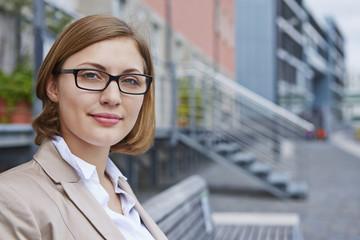 Deutschland, Köln, Geschäftsfrau sitzt auf der Bank