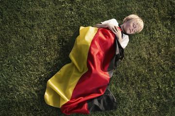 Deutschland, Köln, junge Fußball-Fan schläft in deutsche Flagge eingewickelt