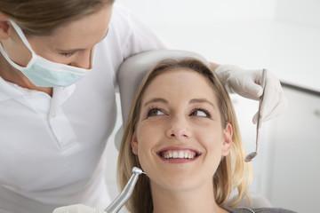 Deutschland, Junge Frau, die ihre Zähne von Zahnarzt untersucht
