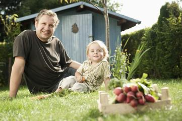 Deutschland, Bayern, Vater und Sohn sitzen im Garten