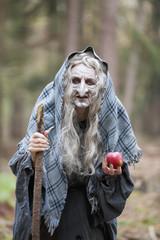 Deutschland, Mönchengladbach, Szene aus Märchen, Hexe hält einen Apfel in den Wäldern