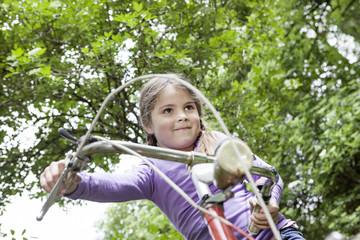 Deutschland, Köln, Mädchen sitzt auf dem Fahrrad am Spielplatz