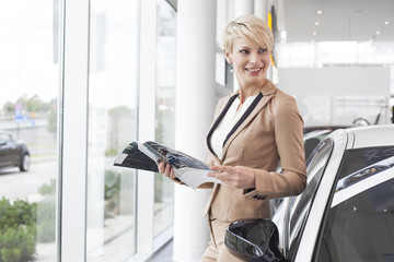 Frau liest Katalog im Showroom des Autohauses
