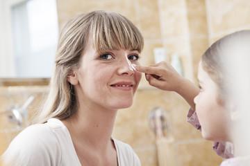 Deutschland, Köln, Tochter, die Creme auftragen Mutter im Badezimmer