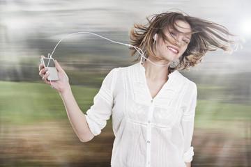 Deutschland, Köln, junge Frau hört Musik auf ipod