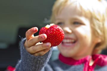 Mädchen mit Erdbeere in der Hand