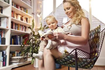 Deutschland, Bonn, Schwangere Mutter Lesen buch mit Sohn im Wohnzimmer