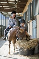 Deutschland, Korchenbroich, Junge und Mädchen reiten mit Mini- Shetland-Pony