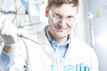Deutschland, Junge Wissenschaftler Pipettieren blaue Flüssigkeit in Reagenzgläser