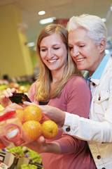 Deutschland, Köln, Damen mit Smartphone und Orangen im Supermarkt