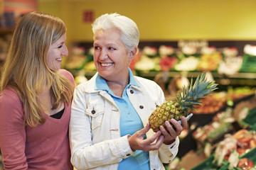 Deutschland, Köln, Frauen mit Ananas im Supermarkt