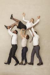 Geschäftsleute tragen Geschäftsfrau im Büro