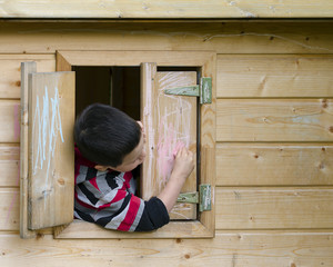 Child in playhouse drawing with chalk