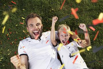 Deutschland, Vater und Sohn, die auf Rasen, tragen Fußballtrikots, Jubel