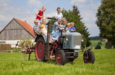 Deutschland, Bayern, Frau mit einer Gruppe von Kindern auf alten Traktor sitzt vor Bauernhaus