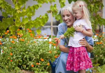 Deutschland, Bayern, Seniorin mit Mädchen im Garten