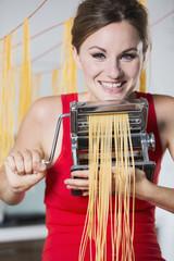 Deutschland, Junge Frau macht Nudeln mit Maschine