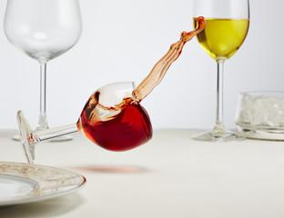 Glas Rotwein auf dem Tisch umfällt