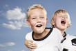 Deutschland, Köln, Zwei Jungs spielen Fußball, tragen Fußballtrikots