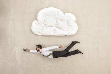 Geschäftsmann mit Handy und unter Wolke Form Kissen fliegen