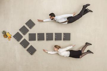 Geschäftsleute fliegen entlang Pfeilzeichen gebildet von Aktenordner