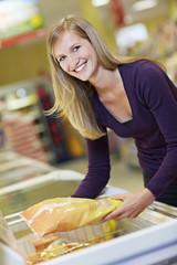Deutschland, Köln, Junge Frau am Gefrierfach im Supermarkt