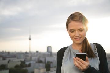 Deutschland, Berlin, junge Frau auf der Dachterrasse, mit Handy