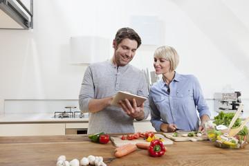Deutschland, München, Senioren Paar die Zubereitung von Speisen, während Sie Tablet PC anschaut