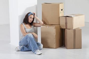 Junge Frau sitzt mit Kartons