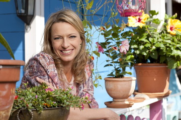lächelnde Frau, staht auf ihrer Terrasse
