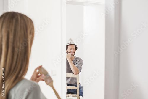 Frau halten Pinsel, während Mann sitzt auf Stuhl