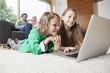 Deutschland, Nürnberg, Mädchen und Jungen mit Laptop im Wohnzimmer