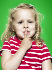 Portrait des kleinen Mädchens mit dem Zeigefinger auf den Lippen