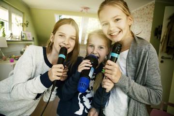 Drei Mädchen singen mit Mikrofon