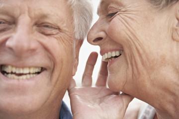 Spanien, Seniorin flüstert in das Ohr des Mannes