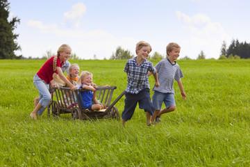 Deutschland, Bayern, Gruppe der Kinder spielen mit Handwagen