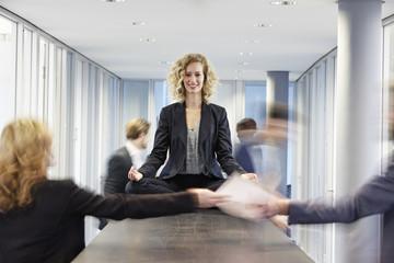 Deutschland, Business-Frau meditiert auf dem Schreibtisch