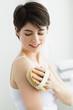 Deutschland, München, junge Frau reinigen Haut mit Bürste