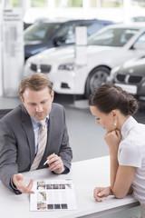 Beim Autohändler, Verkäufer, die Kunden Katalog zeigt